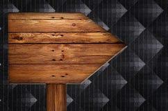 Altes hölzernes PfeilVerkehrsschild auf schwarzem Hintergrund Stockbilder