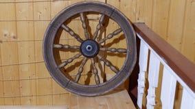 Altes hölzernes Rad auf der Wand der natürlichen hölzernen Beschaffenheit des Hauses Stockbild