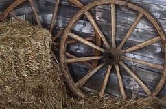 Altes hölzernes Rad auf einem Heu lizenzfreie stockfotografie
