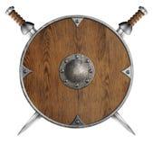 Altes hölzernes rundes Schild und zwei kreuzten Klingen Stockfotografie