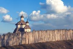 Altes hölzernes rustikales Kirchengebäude und Bretterzaun gegen blaue SK Lizenzfreie Stockfotografie
