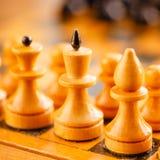 Altes hölzernes Schach, das auf Schachbrett steht Lizenzfreie Stockfotos