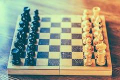 Altes hölzernes Schach, das auf Schachbrett steht Lizenzfreie Stockfotografie