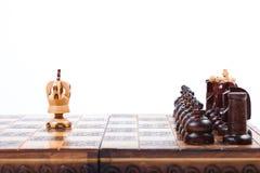 Altes hölzernes Schachbrett mit einsamem König gegen gegenüberliegendes Team, weißen Hintergrund, Kopienraum Stockbilder