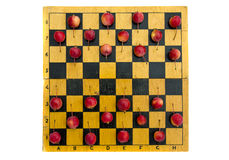 Altes hölzernes Schachbrett mit roten Holzäpfeln Lizenzfreie Stockbilder