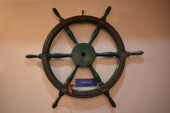 Altes hölzernes Schiffslenkradsteuer auf einer Wand stockbild
