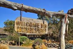 altes hölzernes Schild mit Textwillkommen nach Colorado Springs Hängen an einer Niederlassung Lizenzfreies Stockbild