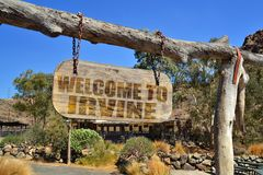 altes hölzernes Schild mit Textwillkommen nach Irvine Hängen an einer Niederlassung lizenzfreie stockfotografie