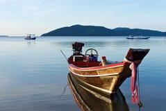 Altes hölzernes thailändisches traditionelles Fischerboot reflektiert im Wasser stockfoto