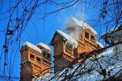 Altes Haus der Kamine mit Schnee Stockfotos