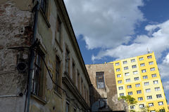 Altes Haus gegen Wiederaufbauenwohnblock stockfotos