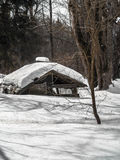 Altes Haus im Wald bedeckt mit Schnee Lizenzfreies Stockfoto
