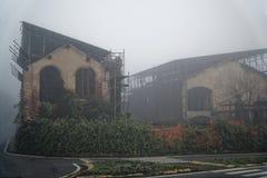Altes Haus mit einem Geist auf dem Straße morgens Horror-Haus im Nebel Altes mystisches Gebäude in totem Baumwald-Halloween-Konze stockfoto