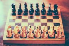 Altes hölzernes Schach, das auf Schachbrett steht Stockbild