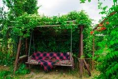 Altes hölzernes Schwingen im grünen Garten Stockfotos