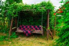Altes hölzernes Schwingen im grünen Garten Stockbild