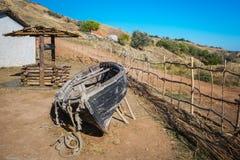 Altes holey Boot, hölzern gut hinter einer hölzernen Hecke auf einem Abhang durch das Meer lizenzfreies stockfoto