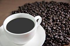 Altes Holz der Kaffeetasse und der Kaffeebohnen auf dem Tisch. Stockfotografie