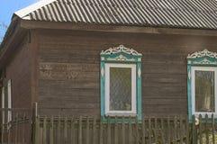 Altes Holzhaus mit geschnitzten Fensterrahmen auf den Fenstern Lizenzfreie Stockbilder