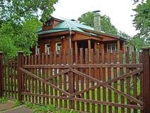 Altes Holzhaus mit grünem Dach und braunem Zaun stockbild