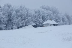 Altes Holzhaus mitten in dem Wald im Winter Stockfotos