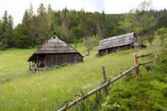 Altes Holzhaus zwei auf einem Abhang, umgeben durch einen Zaun Wald und Berge im Hintergrund Bäume im Wald lizenzfreie stockfotos