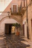 Altes italienisches gelbes Backsteinhaus mit Bogen und Baumtopf und -laterne Mittelalterliches Yard mit balcone und Baum stockfotos