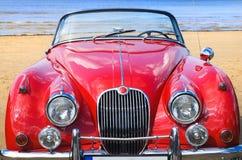 Altes klassisches rotes Auto am Strand Stockbild