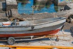 Altes kleines Fischerboot auf Anhänger auf Ufer unter Reparatur Stockbilder