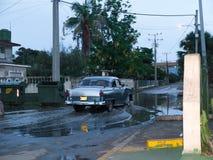 Altes kubanisches Auto, das eine Pfütze kreuzt stockfotos