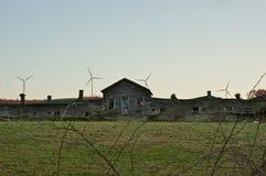 Altes landwirtschaftliches Gebäude zog sich durch moderne Windmühlen zurück Stockbilder