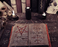 Altes magisches Buch und schwarze Kerzen auf Hexentabelle Lizenzfreie Stockfotos