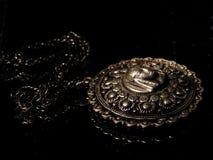 Altes Medaillon in der Dunkelheit stockbild
