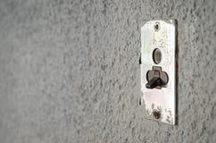 Altes Metall, das elektrischen Schalter auf grauer Wand beleuchtet Stockfotos