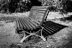 Altes Metall und Holz setzt in einem Garten auf die Bank stockfoto