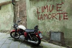 Altes Motorrad, das vor einer Wand mit dem Schreiben steht Stockbild