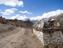 Altes Nepal Mani Stones auf der weißen Backsteinmauer und dem Wanderer, die in Abstand gehen Stockbild
