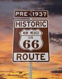 Altes New Mexiko-Zeichen des Weg-66 mit Sonnenaufgang-Himmel Stockbilder