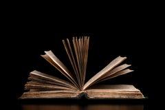 Altes offenes Buch auf einem schwarzen Hintergrund Stockfoto