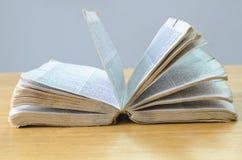 Altes offenes Buch auf hölzerner Tabelle Stockbild