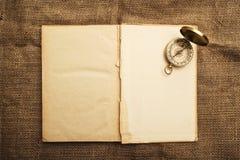 Altes offenes Buch mit Kompass Stockfotografie