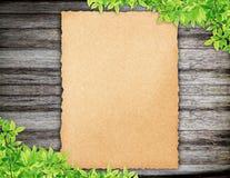 Altes Papier auf Holz und Grünblättern Stockfotos