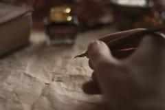 Altes Papier mit einer schreibenden Hand mit der Feder Feder und Bibel auf Holztisch lizenzfreies stockbild