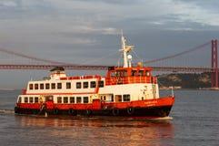 Altes Passagierboot cacilheiro, das den Tajo mit den 25 von April Bridge auf dem Hintergrund in Lissabon kreuzt Stockbild
