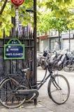 Altes Pedal-Fahrrad in Paris mit altem französischem Straßenschild Lizenzfreies Stockbild