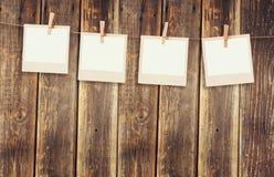 Altes polaroidfoto gestaltet das Hängen an einem Seil mit hölzernem Hintergrund Stockbild