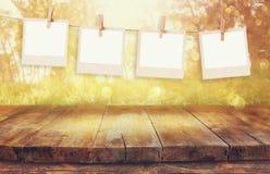 Altes polaroidfoto gestaltet das Hängen an einem Seil mit Tabelle des hölzernen Brettes der Weinlese vor abstrakter Waldlandschaf Stockfotos