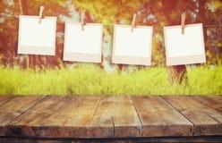 Altes polaroidfoto gestaltet das Hängen an einem Seil mit Tabelle des hölzernen Brettes der Weinlese vor abstrakter Waldlandschaf Stockbild