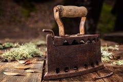 Altes rostiges Eisen auf einem rustikalen Holztisch bügeln stockbilder