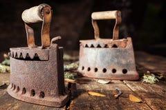 Altes rostiges Eisen auf einem rustikalen Holztisch bügeln stockfoto